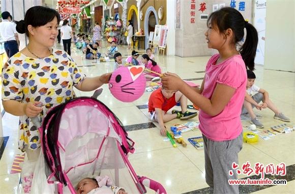 """6月16日,一位市民在""""跳蚤市场""""上选购小学生制作的兔子灯笼.图片"""