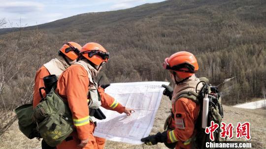 图为奇乾中队消防指战员查看地形。 张林虎 摄